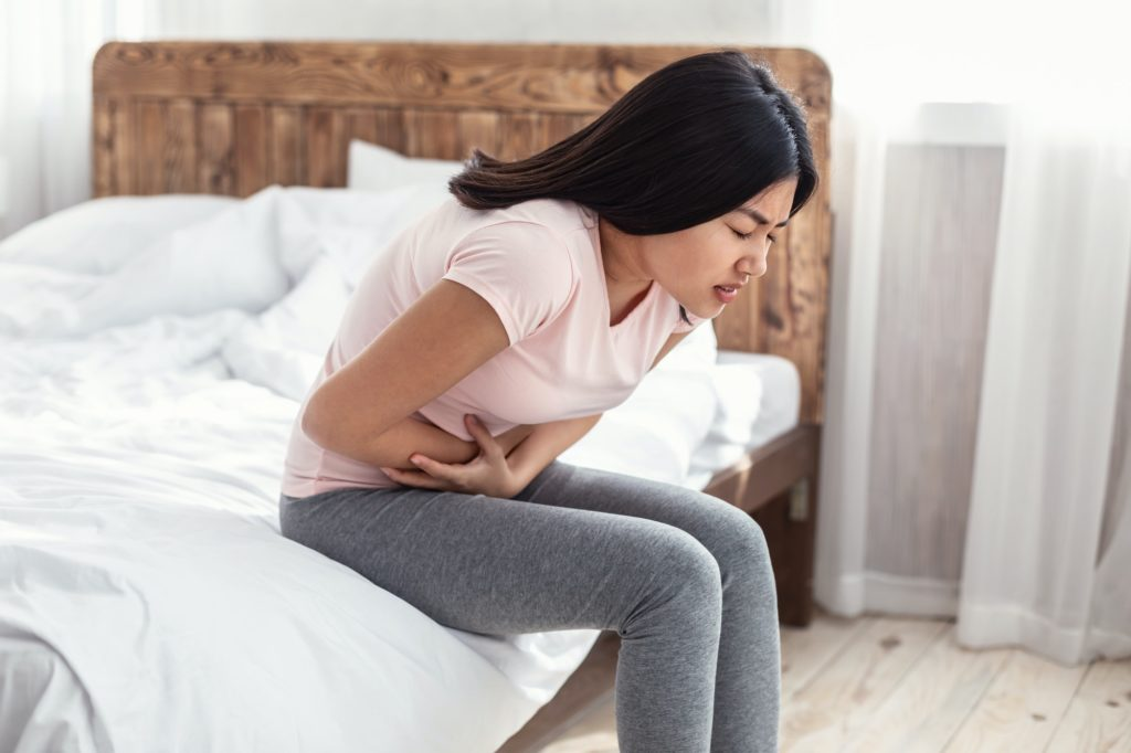 Asian Woman Having Stomachache Suffering From Pain Sitting At Home